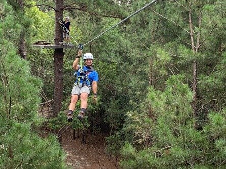 Man on zipline with trees